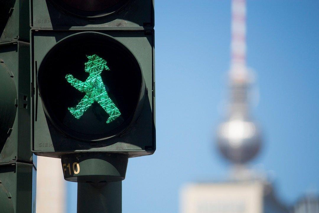 Un semáforo de Berlín muestra al Ampelmännchen con la Torre de Televisión al fondo.