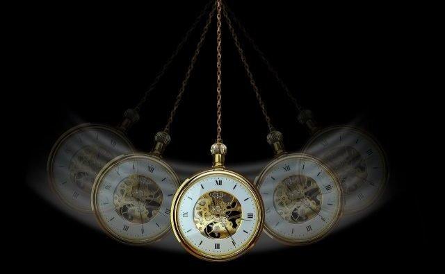 Reloj de bolsillo antiguo colgando y que da la sensación de moverse pendularmente sobre un fondo negro.