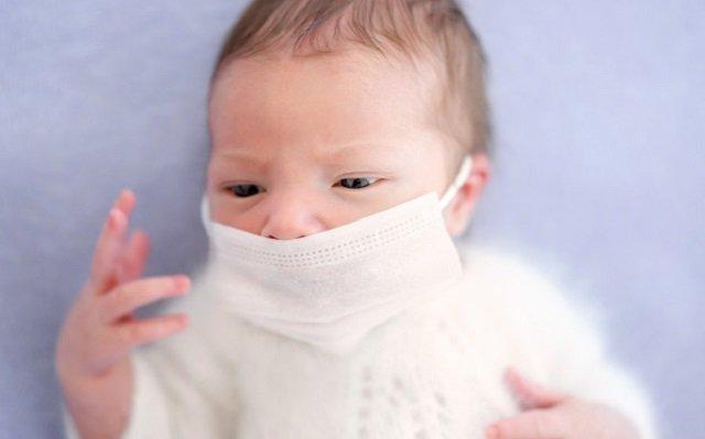 Bebé recién nacido vestido de blanco con mascarilla contra el coronavirus.