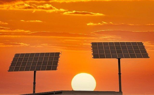 Dos páneles solares se reflejan a contra luz mientras el Sol se oculta en el horizonte detrás de ellos.
