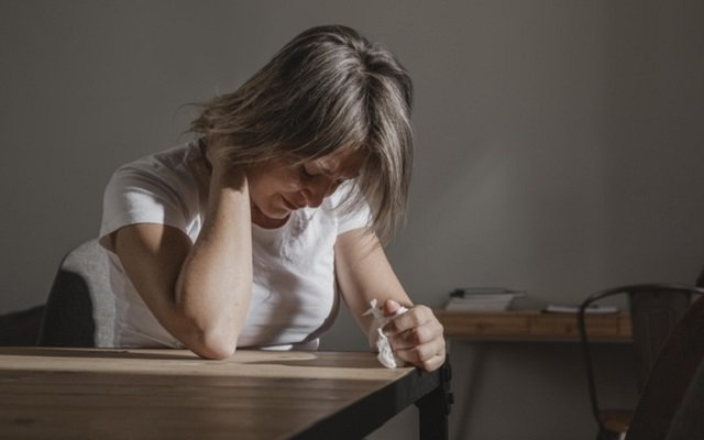 Mujer sentada en una mesa mirando hacia abajo con expresión de angustia y con la mano en el cuello en señal de enfermedad.