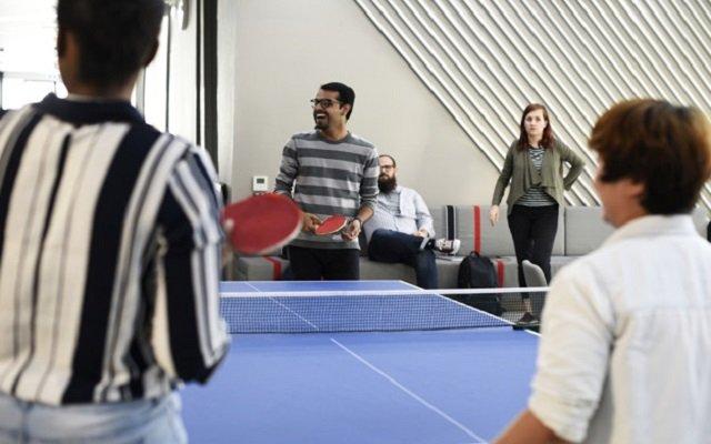 Empleados jugando tenis dentro de una oficina como parte de un ejercicio de integración de equipo.