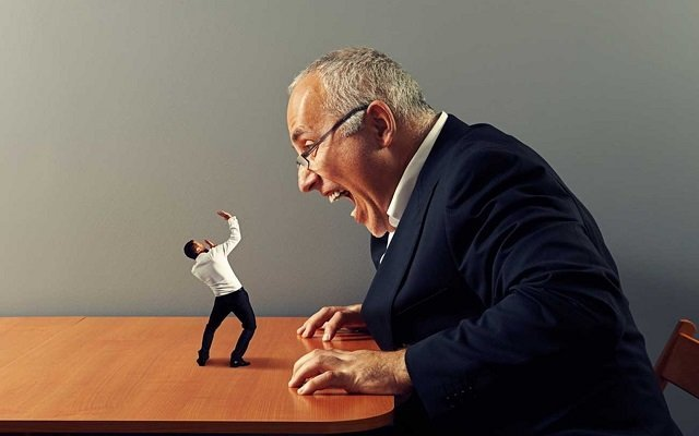 Representación de los malos jefes de las empresas con un hombre de traje gordo y viejo gritando a una versión minimizada de una persona que está parada sobre una mesa con las manos arriba con posición defensiva.