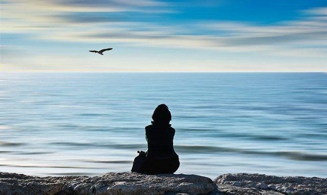 Mujer sentada sola en el medio de una playa, representando los sentimientos de soledad, pero también la sabiduría.