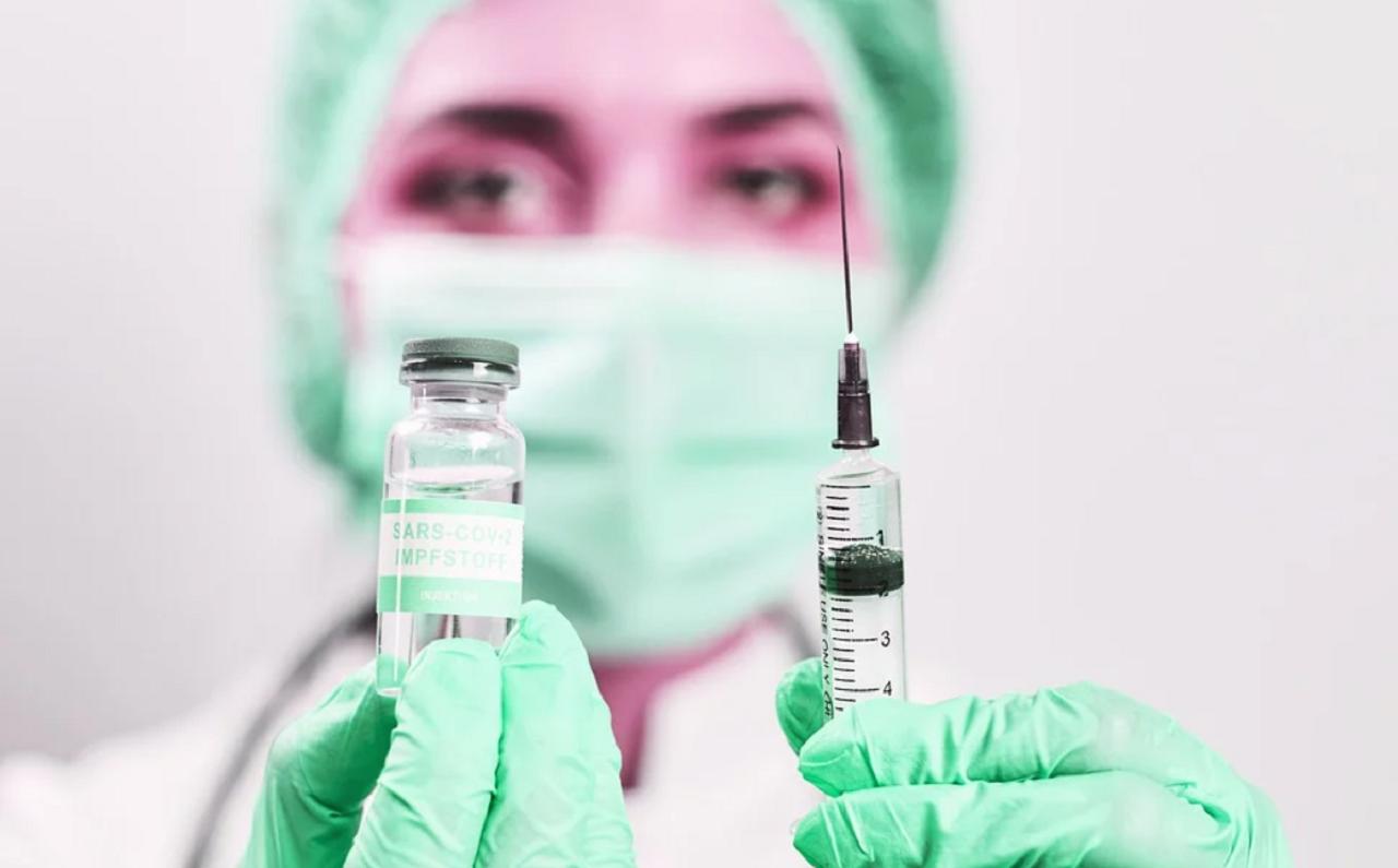 Mujer médico con mascarilla, gorro y guantes, sosteniendo una jeringa y un frasco con una vacuna contra COVID-19.