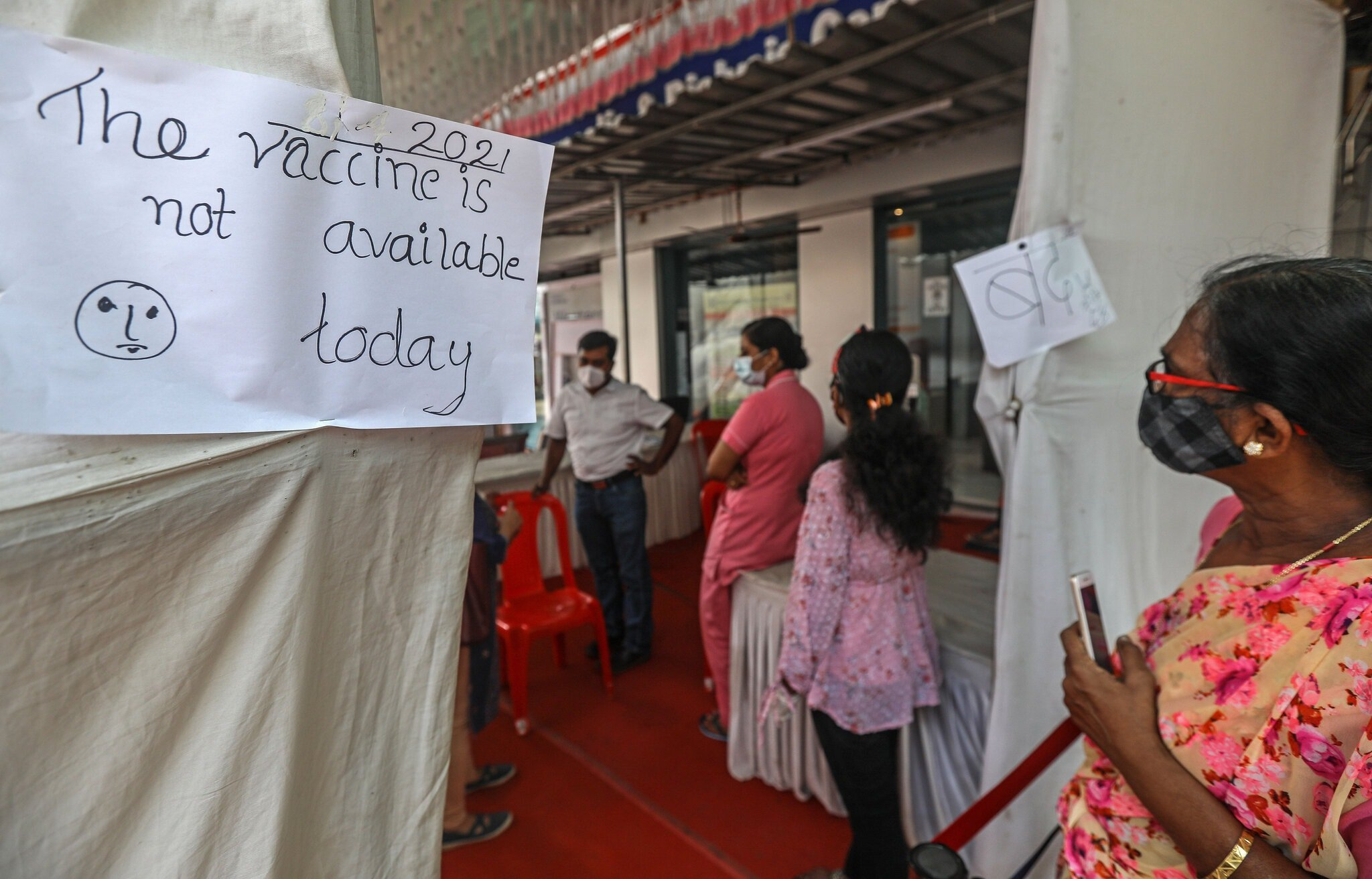 "Centro de vacunación contra COVID-19 en India con un cartel escrito a mano que dice "" Vaccine is not available today""."