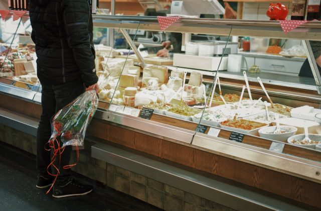 Consumer in front of a display case full of different types of cheeses.