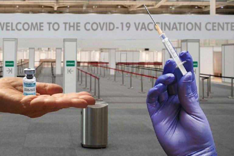 Manos sosteniendo ampollar con vacuna y jeringa frente a un centro de vacunación contra COVID-19.