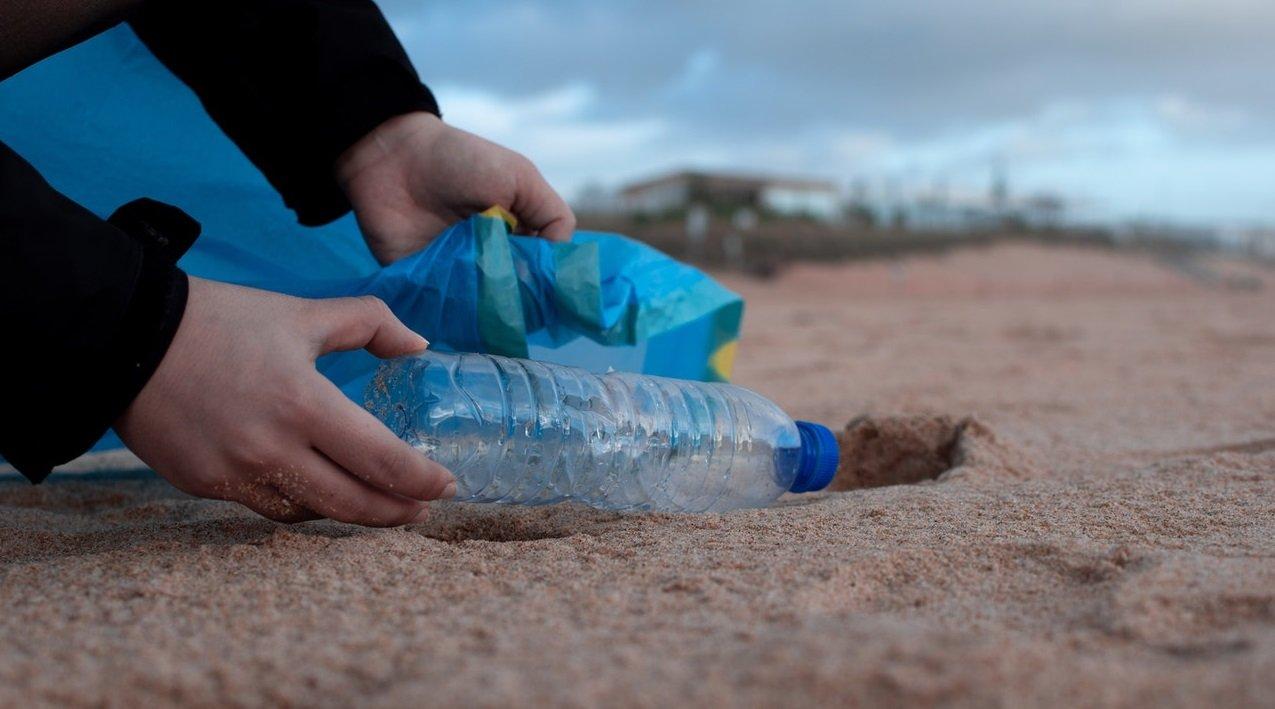 Toma de una persona recolectando basura en la playa